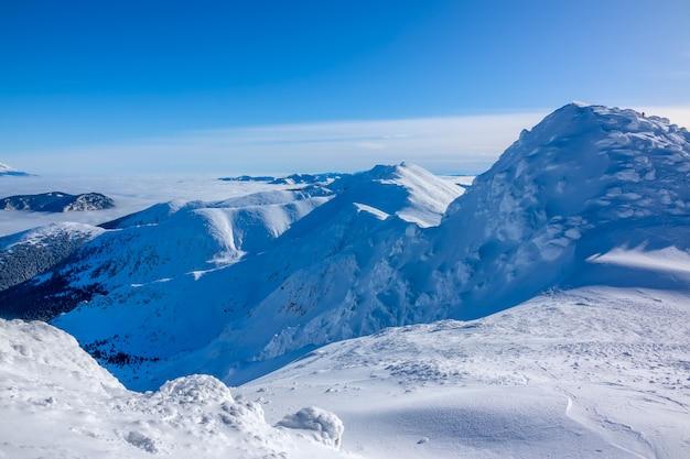 Veel sneeuw op de toppen en hellingen van de winterbergen. zonnig weer en een wolkenloze blauwe hemel