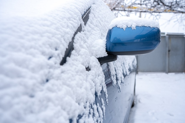 Veel sneeuw op een blauwe auto van dichtbij