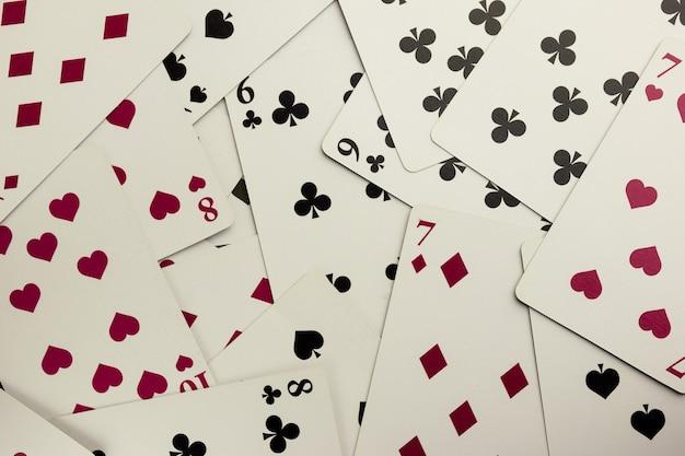 Veel speelkaarten van verschillende kleuren en kleuren zijn verspreid over het frame.