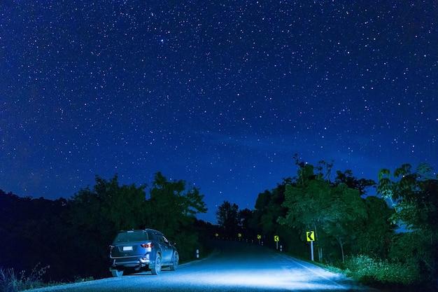 Veel sterren aan de nachtelijke hemel met de auto op de weg