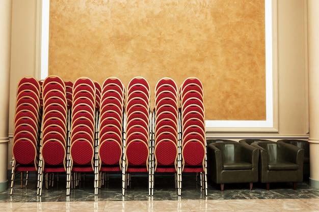 Veel stoelen gevouwen op muur in feestzaal