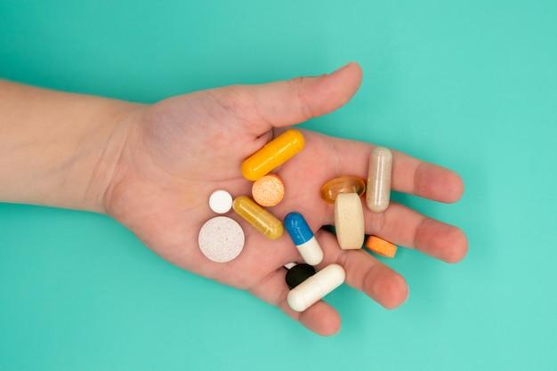 Veel tabletten in de hand van een kind moeten op een blauwe achtergrond worden ingenomen