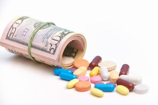Veel tabletten of pillen liggen in de buurt van opgerolde dollars en symboliseren betaalde dure medicijnen en corruptie