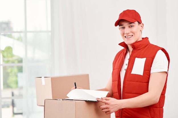 Veel te doen lachende bezorger die staat met pakketten en klembord