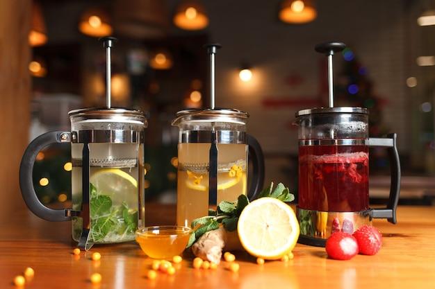 Veel theepotten met gebrouwen fruitthee met verschillende smaken.