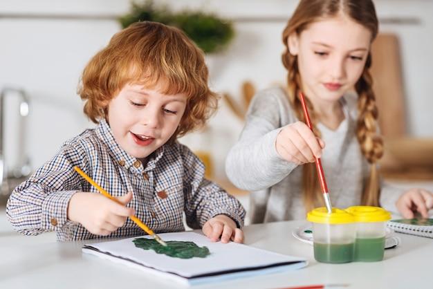 Veel tinten. enthousiaste creatieve schattige jongen die groene aquarellen en een grote borstel gebruikt om groene variatie op zijn papier te creëren terwijl hij deze hobby deelt met zijn zus