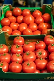Veel tomaten liggen in de vorm van een piramide op elkaar in het zonlicht