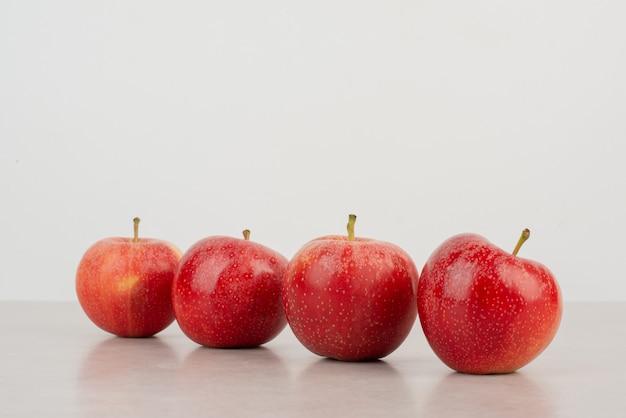 Veel van rode appels op witte tafel.