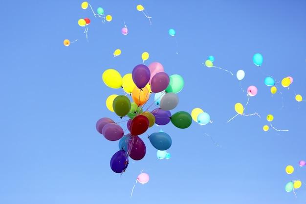 Veel veelkleurige ballonnen vliegen in de blauwe lucht