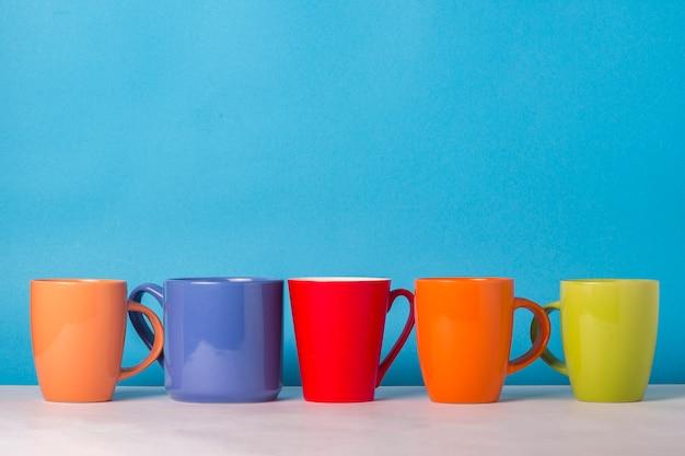 Veel veelkleurige kopjes koffie of thee op een blauwe achtergrond. het concept van een vriendelijk bedrijf, een grote familie, vrienden ontmoeten voor een kopje thee of koffie.