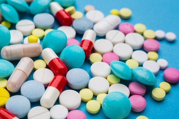 Veel veelkleurige pillen op blauwe achtergrond als een concept van medische behandeling met een recept