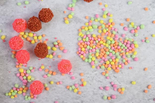 Veel veelkleurige snoepjes geplaatst op een wit oppervlak.