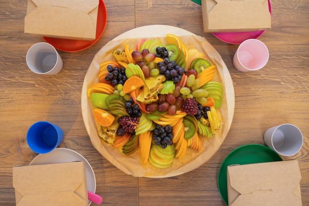 Veel verschillende afhaalmaaltijden pizzadoos koffiekopjes en papieren zakken op lichtgrijze achtergr...