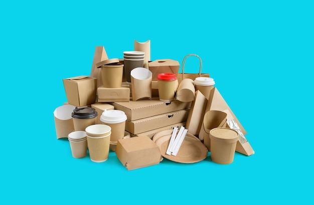 Veel verschillende afhaalmaaltijden, pizzadoos, koffiekopjes in houder en papieren dozen op aquablauwe achtergrond.