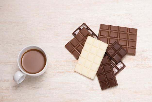 Veel verschillende chocoladereep in doos op witte houten achtergrond