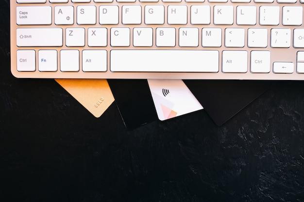 Veel verschillende creditcards op het witte computertoetsenbord. online internetwinkelen tijdens quarantaine-isolatie met creditcardbetaling.