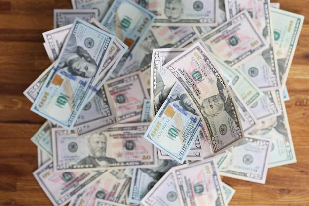 Veel verschillende dollarbiljetten liggend op houten tafel close-up achtergrond illegale verrijking concept