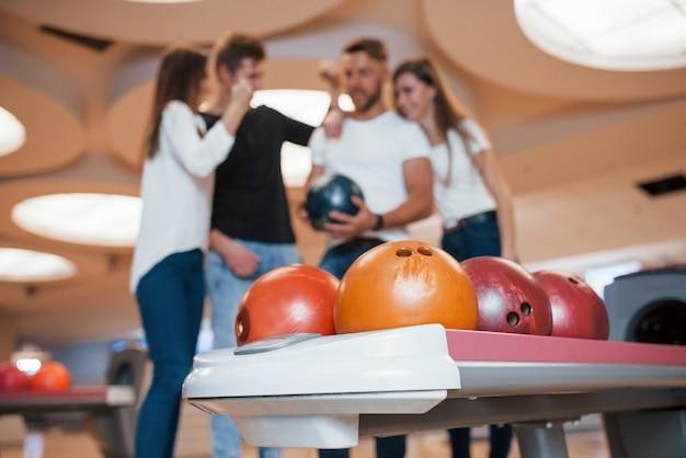 Veel verschillende gekleurde ballen. jonge, vrolijke vrienden vermaken zich in het weekend in de bowlingclub