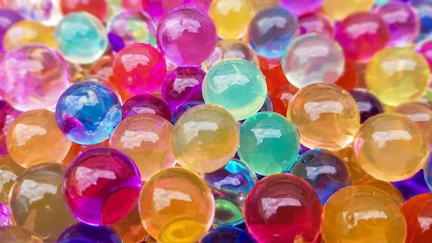 Veel verschillende gekleurde hydrogelballen. set veelkleurige orbis. kristallen waterkralen voor spelletjes. helium ballonnen. kan als achtergrond worden gebruikt. polymeergel silicagel.