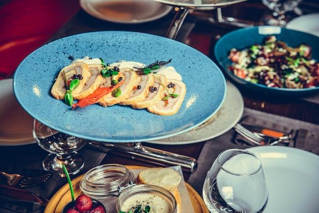 Veel verschillende gerechten in restaurant, witte plaat op tafel met bijgerecht, cracker