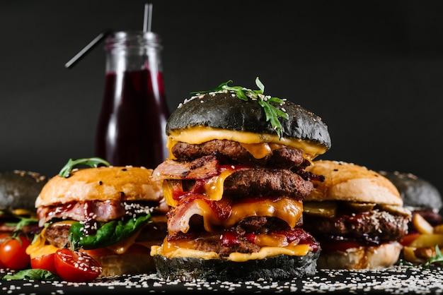 Veel verschillende hamburgers met ingrediënten op een zwart