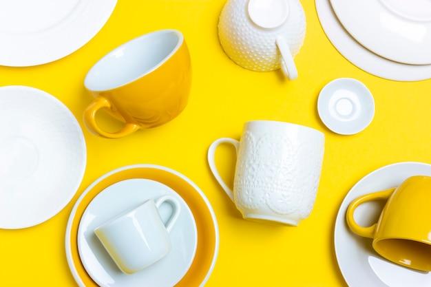 Veel verschillende keramische schalen, lege koffieparen, borden, kopjes op een felgele achtergrond