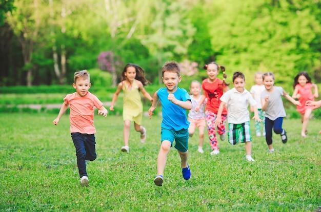 Veel verschillende kinderen, jongens en meisjes die op zonnige zomerdag in vrijetijdskleding in het park lopen