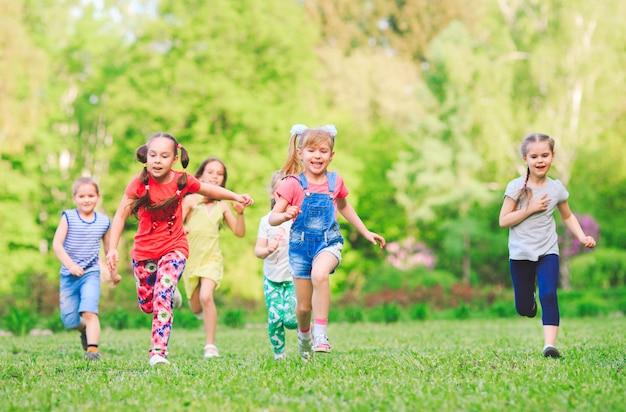 Veel verschillende kinderen, jongens en meisjes lopen in het park op zonnige zomerdag in casual kleding