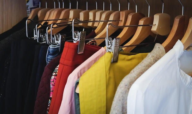 Veel verschillende kleren die in een kledingkast hangen