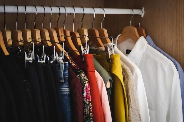 Veel verschillende kleren hangen in een kledingkast