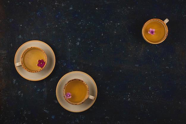 Veel verschillende kopjes thee met violette bloemen op donkerblauwe achtergrond. bovenaanzicht lay-out met kopie ruimte