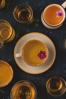 Veel verschillende kopjes thee met violette bloemen op donkerblauwe achtergrond. bovenaanzicht lay-out