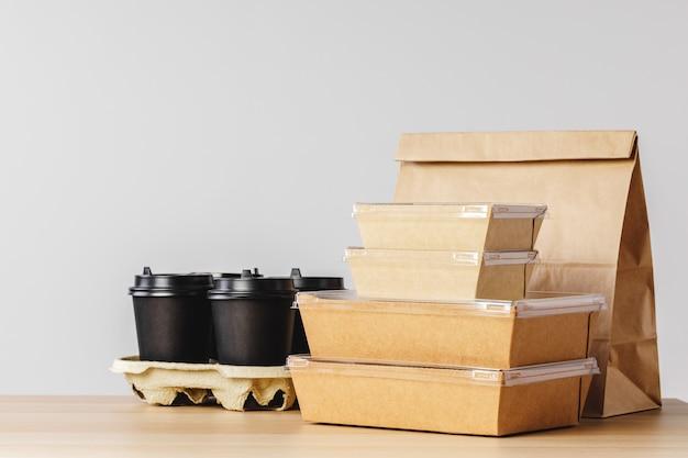 Veel verschillende meeneemcontainers, pizzadoos, koffiekopjes en papieren zakken op lichtgrijs