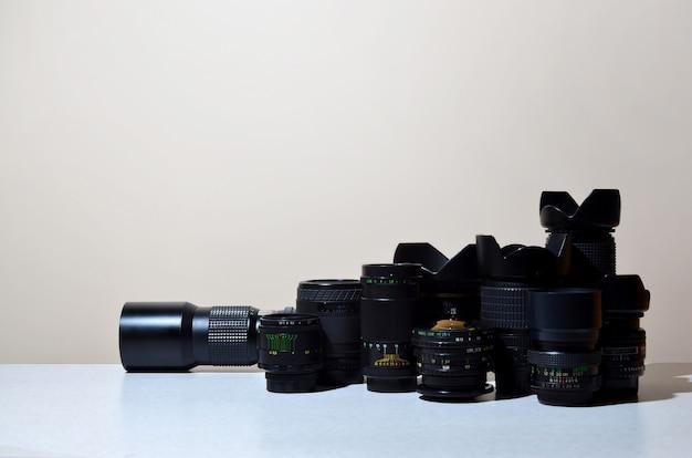 Veel verschillende professionele lenzen voor slr-camera's liggen op een kleurloos bureau
