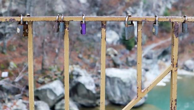 Veel verschillende sloten hangen aan het hek. het gesloten slot op de brug - huwelijkstraditie.