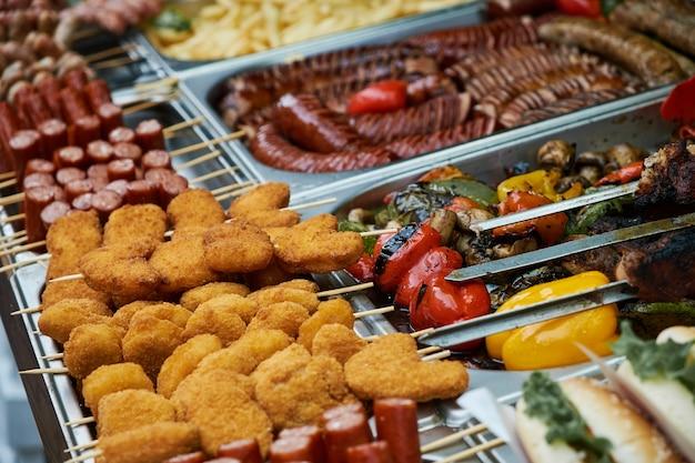 Veel verschillende soorten voedsel in metalen pallets. nuggets op houten stokken
