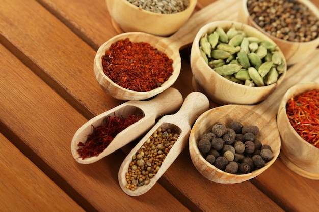 Veel verschillende specerijen en geurige kruiden op houten tafel close-up