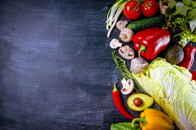Veel verschillende verse groenten op een zwarte houten achtergrond, kopieer ruimte.