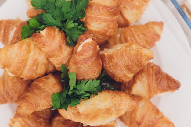 Veel verse croissants op een witte plaat op het buffet in het restaurant.