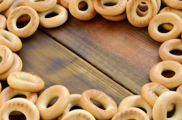 Veel verse gele bagels liggen op het oppervlak van het oude donkere hout.