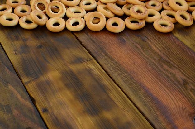 Veel verse gele bagels liggen op het oppervlak van het oude donkere hout