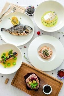 Veel visgerechten op witte tafel. bovenaanzicht