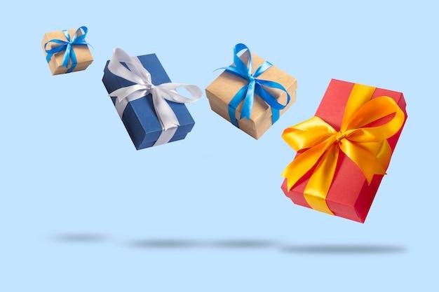 Veel vliegende geschenkdozen op een lichtblauwe ondergrond. concept vakantie, cadeau, verkoop, bruiloft en verjaardag.