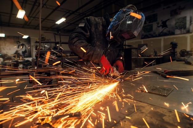 Veel vonken en gefocuste professionele industriële werknemer met beschermingsmasker werken met een elektrische slijper in een stoffenwerkplaats