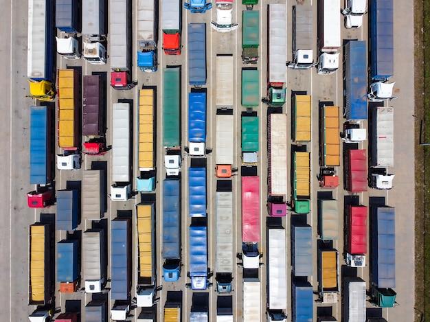 Veel vrachtwagens op de parkeerplaats, een rij vrachtwagens om te lossen