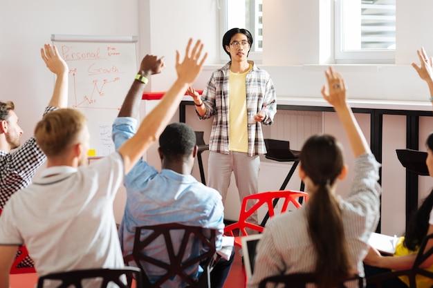 Veel vragen. nieuwsgierige jonge specialisten die hun hand opsteken tijdens het bezoeken van een interessante cursus zelfgroei en vragen hebben aan de spreker