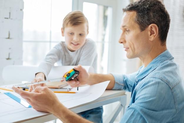 Veel vragen. vrolijke pre-tienerjongen die over het bureau van de vader leunt en zijn vader vraagt hoe hij meetlinten moet gebruiken terwijl de man aan een blauwdruk werkt