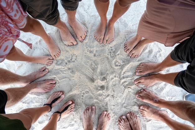 Veel vrouwelijke en mannelijke benen staan samen op zand in de buurt van de zee, zomervakantie concept. bovenaanzicht voeten van mensen of een groep vrienden op het strand