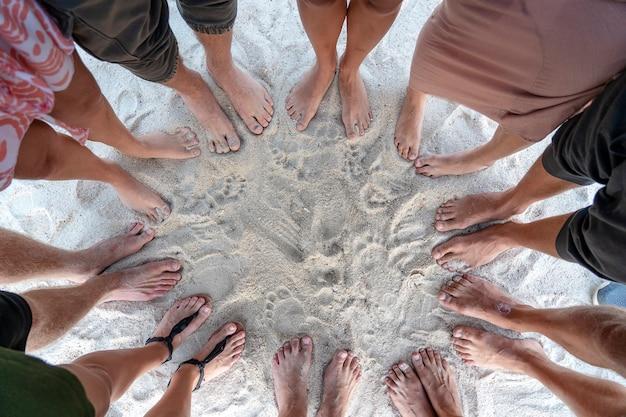 Veel vrouwelijke en mannelijke benen staan samen op zand in de buurt van de zee, zomervakantie concept