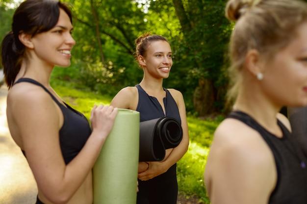 Veel vrouwen met matten, groepsyoga-training in zomerpark